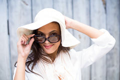 Smiling beautiful brunette wearing straw hat and sun glasses. On wooden plank background Royalty Free Stock Photos
