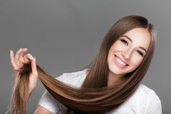 Woman with shiny straight long hair. Smiling beautiful brunette woman with shiny straight long hair. Care of  hair Royalty Free Stock Photography