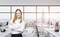 Smiling beautiful business lady with cross hands is standing in a modern panoramic office in New York City. Manhattan sunset view. Stock Photo