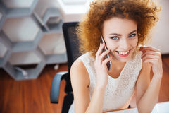 Smiling beautiful business woman talking on mobile phone at workplace Royalty Free Stock Photography