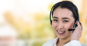 Smiling beautiful businesswoman using headset against ladder used as shelf Royalty Free Stock Photos