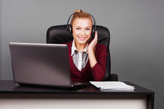 Smiling beautiful call center operator with headphones Stock Photo