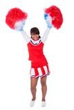 Smiling beautiful cheerleader with pompoms Royalty Free Stock Images