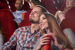 Smiling beautiful couple embracing and watching movie at cinema. Smiling beautiful couple embracing, drinking cola, watching interesting movie at modern cinema royalty free stock photo