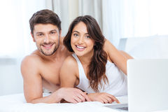 Smiling beautiful couple using laptop and looking at camera Stock Photography