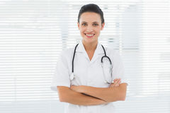 Smiling beautiful female doctor with arms crossed Stock Images