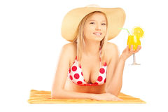 Smiling beautiful female with hat lying on a beach towel and dri Royalty Free Stock Photo