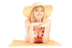 Smiling beautiful female with hat lying on a beach towel and pos Royalty Free Stock Photography