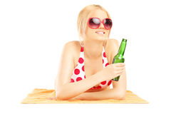 Smiling beautiful female lying on a beach towel and drinking col Stock Images
