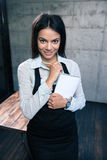 Smiling beautiful female waiter in apron. Standing with notepad and pen in cafe. Looking at camera Royalty Free Stock Image