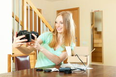 Smiling beautiful girl with blond unpacking new digital camera Royalty Free Stock Photos