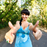 Smiling beautiful girl in blue dress showing  sign OK Royalty Free Stock Images