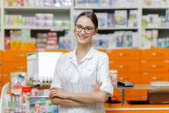 A smiling beautiful girl with dark hair and glasses,wearing a medical overall,stands by the cash desk with her arms royalty free stock image