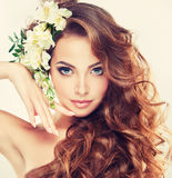Smiling Beautiful girl.Delicate pastel flowers in curly hair. Young gorgeous lady with wavy, dense hair, and charming look.Spring freshness. Girl with delicate royalty free stock photos