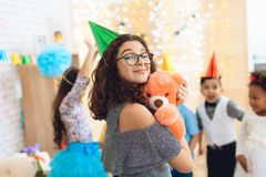 Smiling beautiful girl in green festive hat gently hugs teddy bear at celebration. Concept of children`s holiday. Happy birthday party Stock Photo