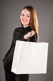 Smiling beautiful girl holding paper bag. Grey background Royalty Free Stock Photography