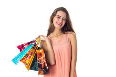 Smiling beautiful girl holds in his hand bags isolated on white background Royalty Free Stock Images