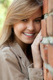 Smiling beautiful girl leaning on wall Stock Photo