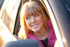 Smiling beautiful girl looks out of a car window Royalty Free Stock Images