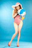 Smiling beautiful girl pin-up in a pink bikini with beach ball Royalty Free Stock Photography