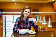 Smiling beautiful girl in a plaid shirt drinking tea in a cafe Stock Images