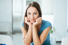 Smiling beautiful girl posing at desk Stock Photos