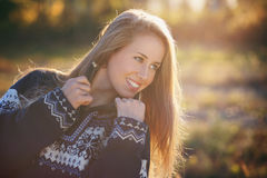 Smiling beautiful girl posing with heavy sweater Stock Photos