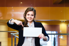 Smiling beautiful girl shows on blank white card Stock Image