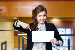 Smiling beautiful girl shows on blank white card Stock Photo
