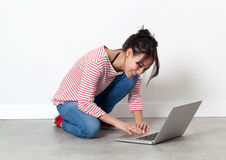 Smiling beautiful girl sitting on the floor, working on computer Stock Photography