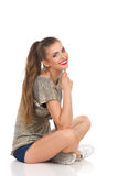 Smiling Beautiful Girl Sitting With Legs Crossed Stock Image