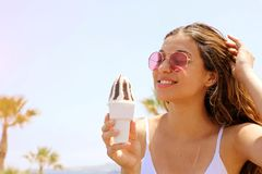 Smiling beautiful girl with sunglasses on the beach eating ice cream with palm trees on the backgroud. Summer holidays concept royalty free stock photos