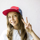 Smiling beautiful girl teenager in a baseball cap and white t-shirt. On a light background Stock Photography