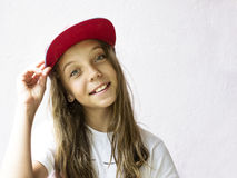 Smiling beautiful girl teenager in a baseball cap and white t-shirt. On a light background Stock Photos