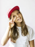 Smiling beautiful girl teenager in a baseball cap and white t-shirt. On a light background Royalty Free Stock Photography