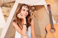Smiling beautiful hippy girl resting at the beach tent. At campsite Royalty Free Stock Images