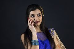 Smiling beautiful indian girl calling with smart phone. Young female model wears jewelry sets and traditional blue clothes Stock Photos