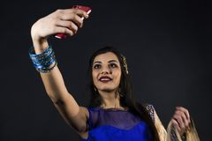 Smiling beautiful indian girl takes a selfie. With smart phone. young female model wears jewelry sets and traditional blue clothes Royalty Free Stock Photos
