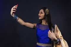 Smiling beautiful indian girl takes a selfie. With smart phone. young female model wears jewelry sets and traditional blue clothes Royalty Free Stock Images