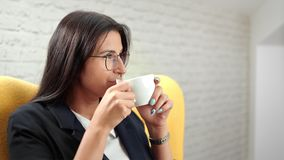Smiling beautiful informal business woman relaxing drinking coffee at white room background stock video