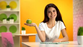 Smiling beautiful lady holding green apple in hand sitting at table, health care royalty free stock image