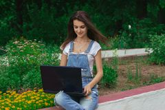 Smiling beautiful lady sitting in a flower park on street prints on your laptop royalty free stock photos