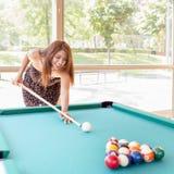 Smiling beautiful latin young woman playing pool. Stock Photography