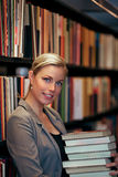 Smiling beautiful librarian. Or student carring a pile of books in a library as she either replaces them on the shelves or removes them for further research Royalty Free Stock Image