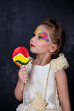 Smiling beautiful little girl with lollipop in white dress red lips with painted face at dark background. Children love candy royalty free stock photos
