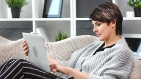 Smiling beautiful mature female relaxing at cozy home chatting using laptop pc medium close-up. Adorable domestic woman enjoying online shopping looking at stock footage
