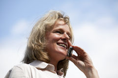 Smiling beautiful mature woman with cellphone. A smiling beautiful mature blond woman phoning with her cellphone Royalty Free Stock Photo