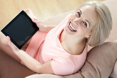Smiling beautiful middle-aged woman sitting on couch with a tablet, considering new idea. Smiling beautiful middle aged woman sitting on couch with tablet Stock Photos