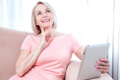 Smiling beautiful middle-aged woman sitting on couch with a tablet, considering new idea. Stock Photos