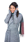 Smiling beautiful model wearing winter clothes listening to music Stock Image